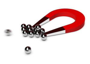 Magnet attracting silver spheres representing inbound marketing