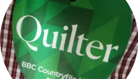 Quilter event badge on checked shirt background - But what do they do?